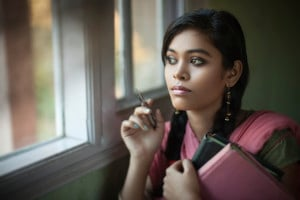 A young person is standing by a window in a school, looking out serenely. They are holding pink and black notebooks and a pen. They are wearing a pink and green sari.