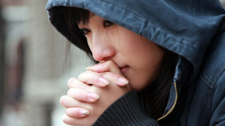 A person wearing a dark-hooded jacket appears worried, with their hands laced and touching their face.