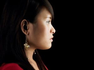 Profile of someone on a black background. They have long black hair, dangling gold earrings, and a serious expression.