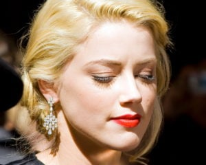 The image features a portrait of Amber Heard in formal attire. Source: Wikipedia