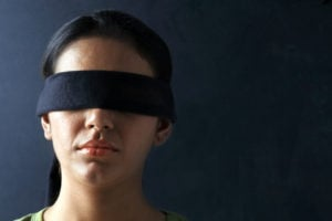 A person from the neck up, facing straight ahead with a blindfold on.