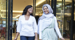 Two people – one wearing a head scarf and one without – walk out of a shopping mall, smiling at each other.