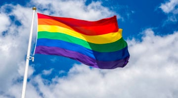 A rainbow flag flying in the wind with a cloudy blue sky in the background.