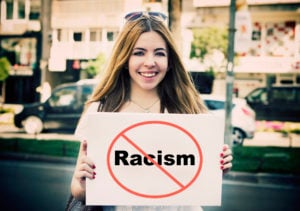 "A person standing in a street, smiling and holding a white placard with the word ""Racism"" in a cross-out circle."
