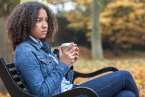 A person sits on a bench holding a cup of coffee, looking worried.