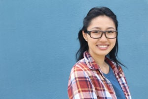 A person in a plaid shirt and glasses smiles into the camera.