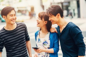 Three people smiling at one another as they walk down a street together.