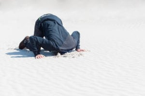 A person at the beach on their hands and knees with their head stuck in the sand.