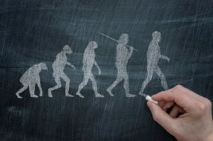 A hand holding a piece of chalk next to a blackboard with an illustration of the evolution of humans.