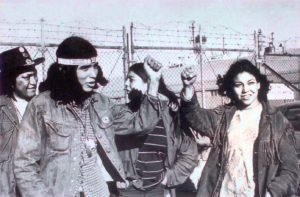 "Native activists at the 1969 Occupation of Alcatraz Island raise their fists. Image credit: ""The Mouse That Roared."""