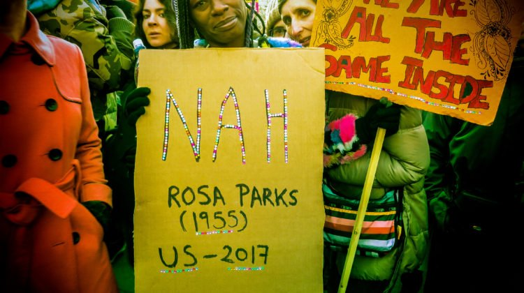 "A photo from a march. One protester holds a sign that reads ""We are all the same inside,"" while the protester in front of them holds a sign that reads ""Nah — Rosa Parks (1955); US – 2017. Image credit: ""DC Women's March"" by Liz Lemon/Flickr."