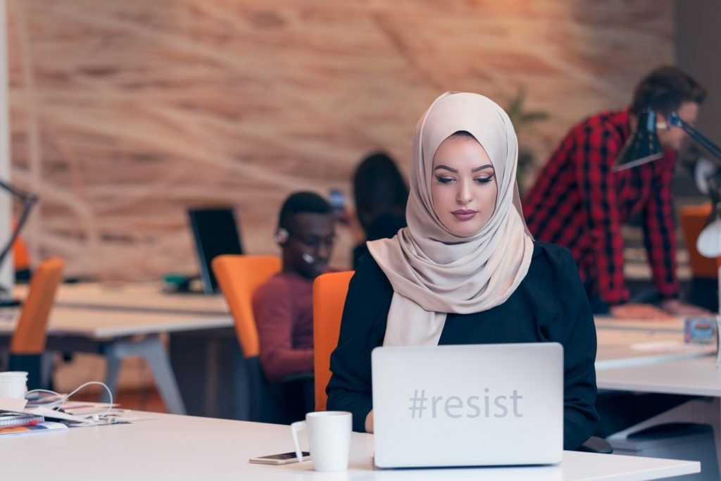 "A person wearing a hijab sits at their desk with coworkers in the background. Their laptop reads ""#resist."" Image source: Thinkstock; text added by Everyday Feminism."
