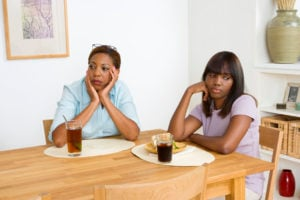 A parent and child look away from each other sadly at the dinning table.