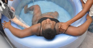 A pregnant person lies in a birthing pool, supported by two midwives.