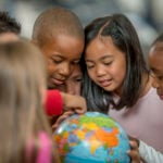 A group of schoolchildren gather around a globe.