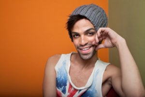 A person wearing a gray beanie and a tank top smiles, their hand resting against their cheek.