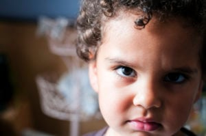 An angry child looks at the viewer; the background is out of focus.